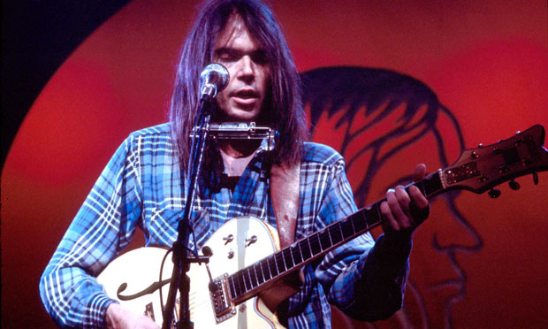 Neil Young performing on stage at the Rainbow Theatre in London in 1973